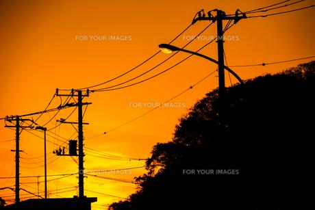 夕焼けと電線と建物のシルエットの写真素材 [FYI01244711]