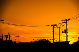 夕焼けと電線と建物のシルエットの写真素材 [FYI01244712]