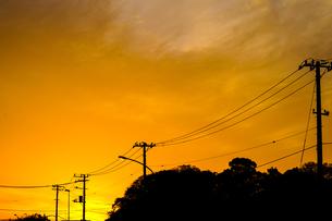 夕焼けと電線と建物のシルエットの写真素材 [FYI01244713]