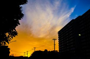 夕焼けと電線と建物のシルエットの写真素材 [FYI01244714]