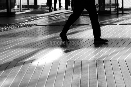 ウッドデッキを歩く人々の影の写真素材 [FYI01245534]