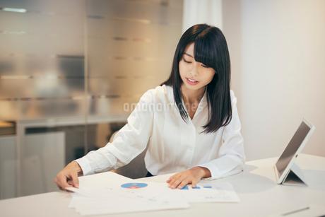 オフィス。資料を眺めるOL女性の写真素材 [FYI01245708]