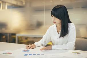 オフィスで資料を指さししながら見るOL女性の写真素材 [FYI01245713]
