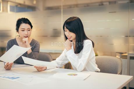 オフィスで資料について話すOL女性2人の写真素材 [FYI01245718]
