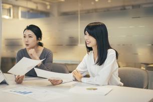 オフィスで資料について話すOL女性2人の写真素材 [FYI01245719]