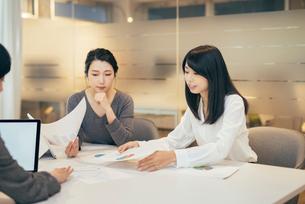 オフィスで資料について話すOL女性3人の写真素材 [FYI01245720]