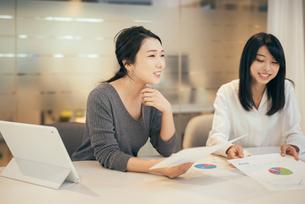 オフィスで資料について話すOL女性2人の写真素材 [FYI01245721]