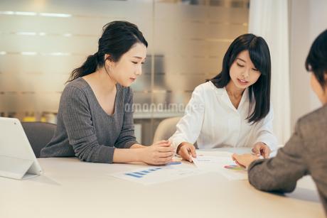 オフィスで資料について話すOL女性3人の写真素材 [FYI01245722]