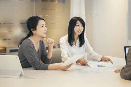 オフィスで資料について話すOL女性2人の写真素材 [FYI01245723]