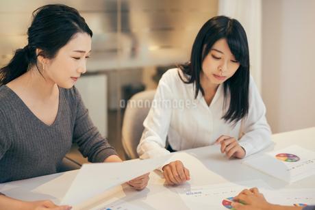 オフィスで資料について話すOL女性2人の写真素材 [FYI01245726]