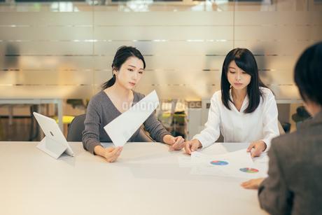 オフィスで資料について話すOL女性2人の写真素材 [FYI01245727]