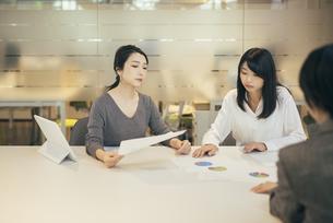 オフィスで資料について話すOL女性2人の写真素材 [FYI01245728]