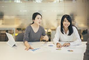 オフィスで資料について話すOL女性2人の写真素材 [FYI01245729]