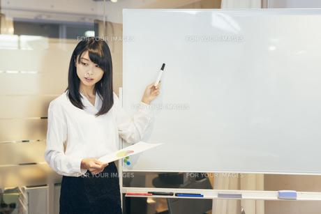 オフィス。ホワイトボードで資料を説明するOL女性の写真素材 [FYI01245738]