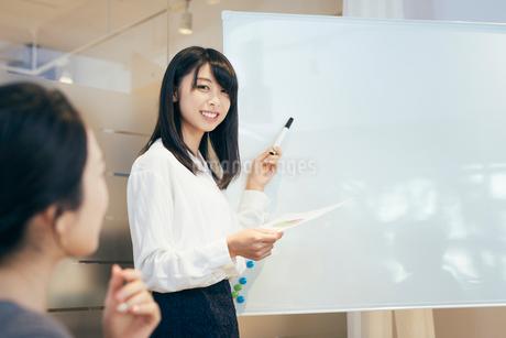 オフィス。ホワイトボードで資料を説明するOL女性の写真素材 [FYI01245739]
