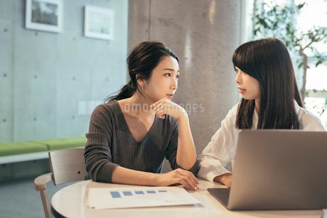オフィス。パソコンと資料について話し合うOL女性2人の写真素材 [FYI01245751]