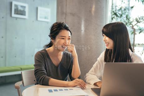 オフィスで資料とパソコンを見るOL女性2人の写真素材 [FYI01245753]