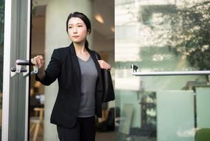 オフィスのガラスドアを開けているOL女性の写真素材 [FYI01245763]
