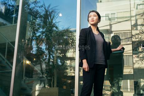 オフィスの外。OL女性がドアに手をかけている。ほほ笑みの写真素材 [FYI01245764]