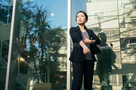 オフィスの外。OL女性がドアの前で腕まくりをしているの写真素材 [FYI01245765]