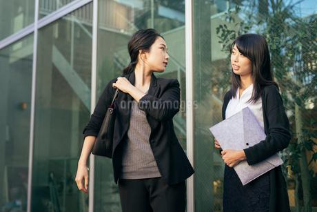 オフィスの外。OL女性2人が会話しているの写真素材 [FYI01245769]