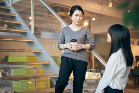 コーヒー。階段で話すOL女性2人。の写真素材 [FYI01245771]