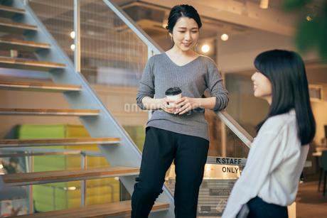 コーヒー。階段で話すOL女性2人。の写真素材 [FYI01245772]