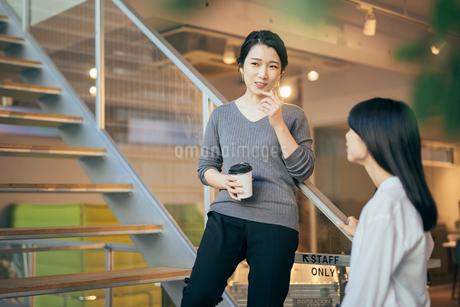 コーヒー。階段で話すOL女性2人。の写真素材 [FYI01245774]