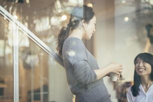 コーヒー。話すOL女性2人。窓越しの写真素材 [FYI01245777]