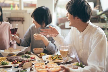ホームパティー。グラスを持ちながら談笑する男女。の写真素材 [FYI01245854]