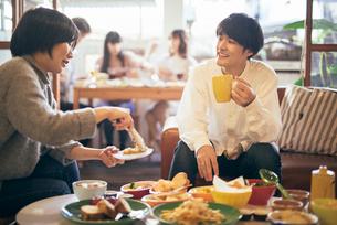 カフェ。マグカップを持っている。談笑中の男女。取り分ける女性の写真素材 [FYI01245870]