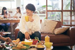 カフェ。マグカップを持っている談笑中の男性の写真素材 [FYI01245874]