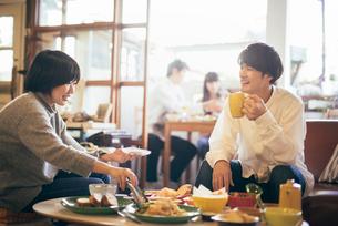 カフェ。マグカップを持っている談笑中の男女の写真素材 [FYI01245875]