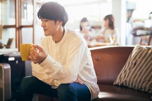 カフェ。マグカップを持つ談笑中の男性の写真素材 [FYI01245877]