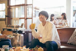 カフェ。マグカップを持つ談笑中の男性の写真素材 [FYI01245879]