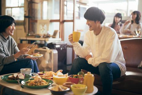 カフェで談笑中の男女。マグカップを持つ男性。取り分ける女性の写真素材 [FYI01245880]