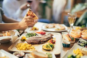 ホームパーティー。ピザを持つ手。料理にピント合わせ(アップ)の写真素材 [FYI01245893]