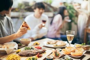 ホームパーティー。ピザを持つ手。料理にピント合わせの写真素材 [FYI01245894]