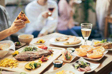 ホームパーティー。ピザを持つ男性の手。料理にピント合わせの写真素材 [FYI01245895]