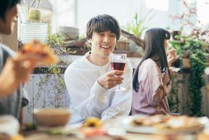 ホームパーティー。ワインを持ちながら談笑する男性の写真素材 [FYI01245896]