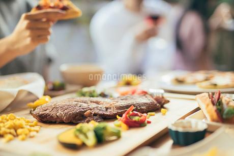 ホームパーティー。ピザを持つ手元。ステーキにピント合わせ。の写真素材 [FYI01245897]
