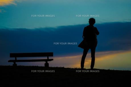 日没の丘に立つ男性のシルエットの写真素材 [FYI01246265]