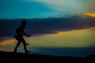 日没の丘に立つ男性のシルエットの写真素材 [FYI01246266]