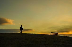 日没の丘に立つ男性のシルエットの写真素材 [FYI01246270]