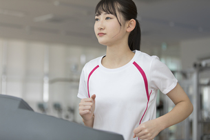 ランニングマシンで走る日本人女性の写真素材 [FYI01246303]