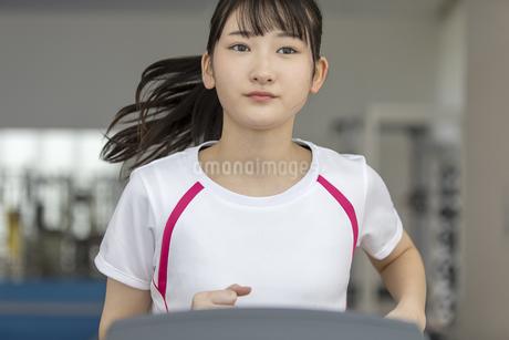 ランニングマシンで走る日本人女性の写真素材 [FYI01246305]