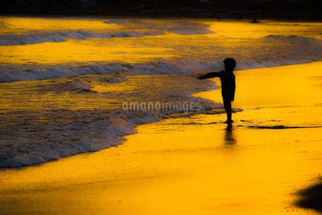 夕暮れの波打ち際で遊ぶ子供の写真素材 [FYI01246717]