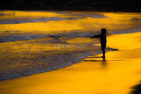 夕暮れの波打ち際で遊ぶ子供の写真素材 [FYI01246718]