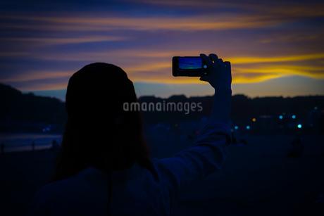 スマホで夕暮れを撮る女性の写真素材 [FYI01246719]