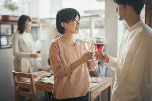 ホームパティーで笑顔で乾杯する男女。女性にピント合わせ。背景に複数人の写真素材 [FYI01248114]